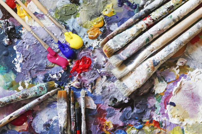 Paintbrushes and fresh paint on artist's palette — Stock Photo