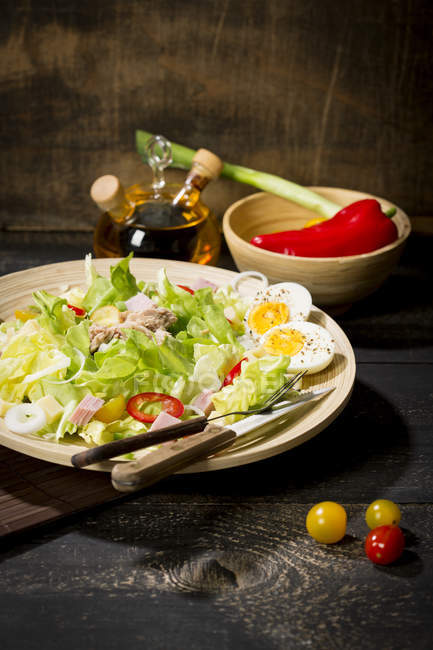 Plate of butterhead lettuce with boiled egg, spring onions, red bell pepper and tuna, dark wooden background — Stock Photo