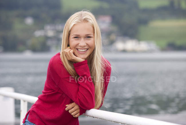 Portrait of smiling teenage girl wearing red pullover — Stock Photo