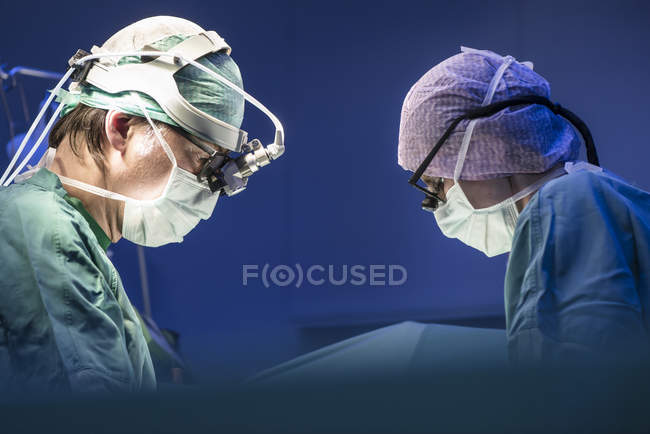 Side portrait of two surgeons during a surgery — Stock Photo