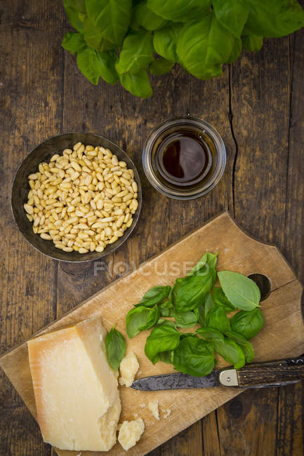 Pesto Genovese, fresh basil leaves, parmesan, pine nuts, olive oil on wooden surface, top view — Stock Photo