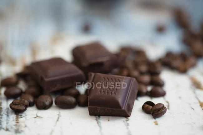 Les grains de café torréfiés et des morceaux de chocolat noir sur bois — Photo de stock
