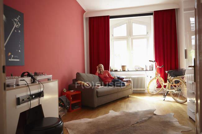 Молода жінка розслабляючий на канапі в домашніх умовах — стокове фото