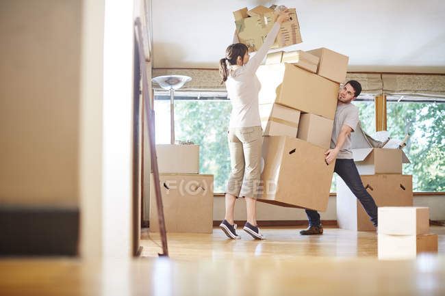 Couple moving house stacking boxes — Stock Photo