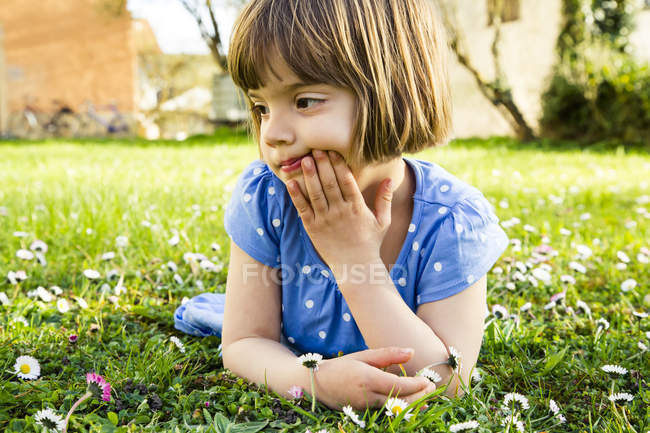 Nachdenkliches kleines Mädchen liegt auf einer Wiese — Stockfoto