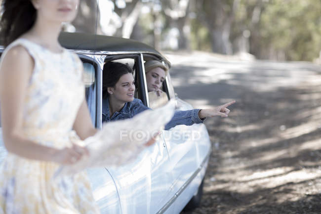 Young women on road trip with friends looking for directions — Stock Photo