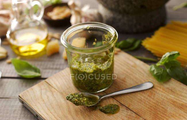 Préserver le bocal de pesto au basilic maison avec cuillère sur planche à découper — Photo de stock