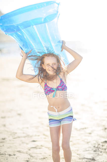 Girl on the beach smiling and holding a lilo — Stock Photo