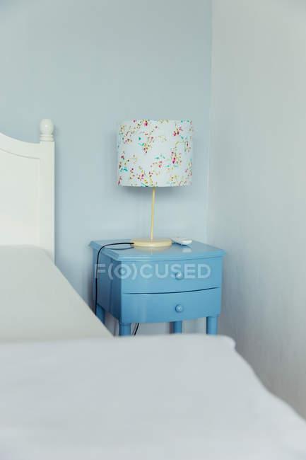 Candeeiro de mesa e cabeceira azul do armário no quarto de uma casa de férias — Fotografia de Stock
