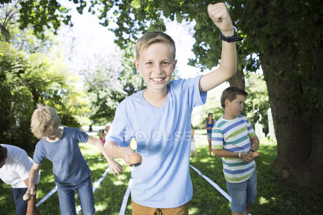 Boy winning in an egg-and-spoon race in garden — Stock Photo