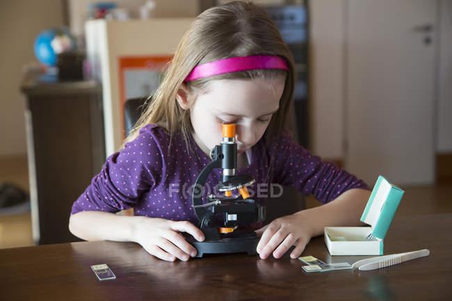 Kleines mädchen mit mikroskop am schreibtisch zu hause u im feld