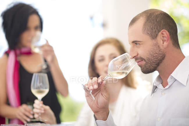 Man smelling white wine on a wine tasting session — Stock Photo