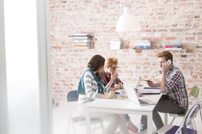 Trois jeunes gens d'affaires travaillant dans la salle de conférence — Photo de stock