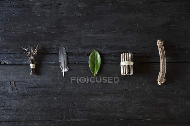 Row of organic natural material on black wood — Stock Photo