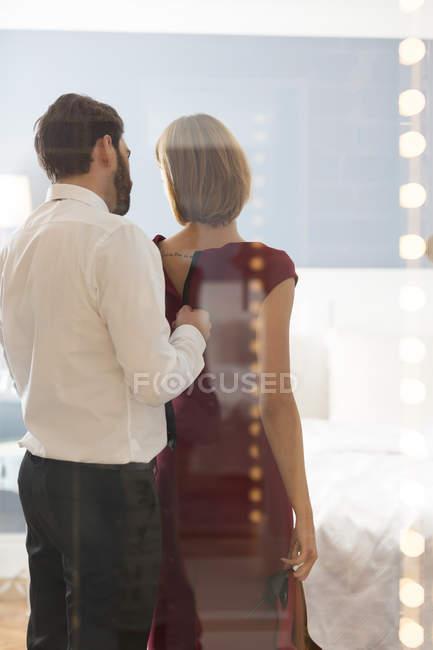 Мужчина расстегивает женское платье в спальне — стоковое фото