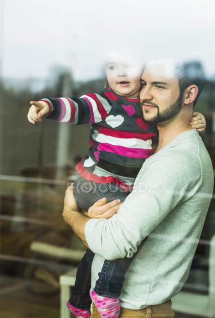 Vater und Tochter schauen zu Hause aus dem Fenster — Stockfoto