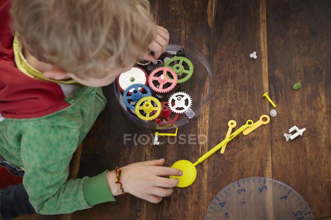 Вид зверху блондин хлопчик складання іграшки годинник — стокове фото