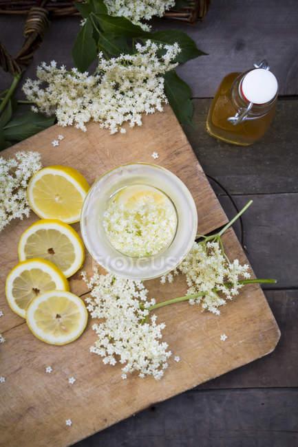 Elderflower sirup, slices of lemon and elderflowers, top view — Stock Photo