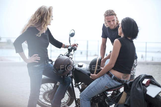 Мужчина и две женщины вокруг мотоциклов — стоковое фото