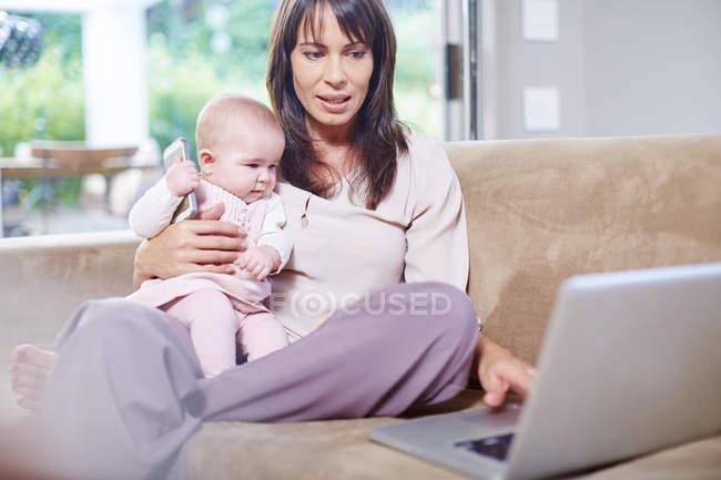 Матері сидить з дитиною на дивані і працюють на ноутбук — стокове фото
