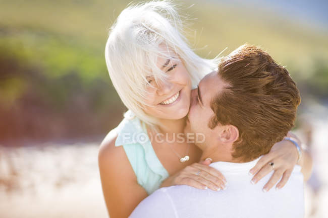 Young couple embracing on the beach — Stock Photo