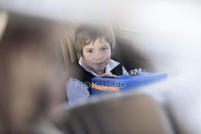 Menina sentada no carro com o saco de escola — Fotografia de Stock