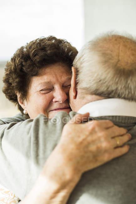 Senior couple Hugging  ta home — Stock Photo