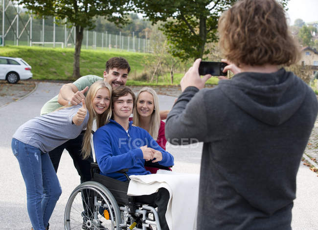 Young man taking a photo of his friends with smartphone — Stock Photo