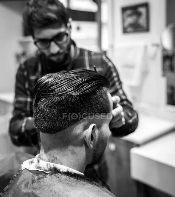 Peluquería cortando el pelo de un joven en una peluquería - foto de stock