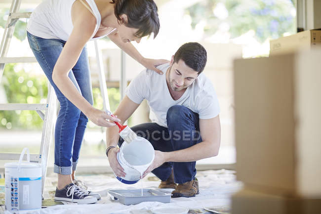 Couple Painting In New Home Together Stock Photo