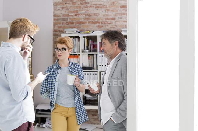 Tres personas de negocios hablando en la oficina moderna - foto de stock