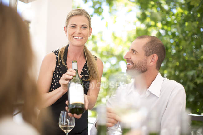 Woman presenting bottle of wine on a wine tasting session — Stock Photo