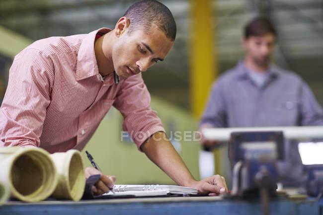 Homem em oficina escrevendo ao lado de tubo de encanamento com colega no fundo — Fotografia de Stock