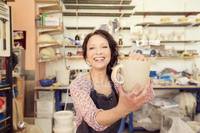 Retrato de oleiro sorridente no estúdio segurando jarro — Fotografia de Stock