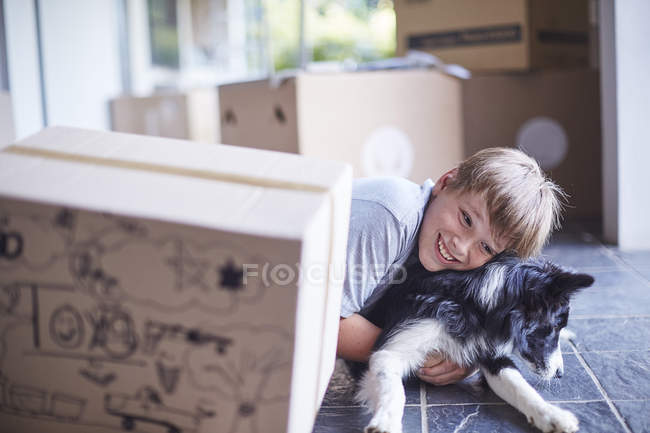 Мальчик играет со своей собакой в новом доме — стоковое фото