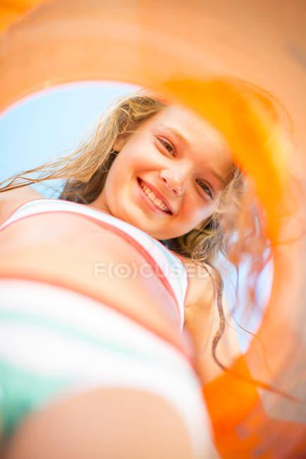 Lächelndes Mädchen am Strand mit orangefarbenem Schwimmreifen — Stockfoto