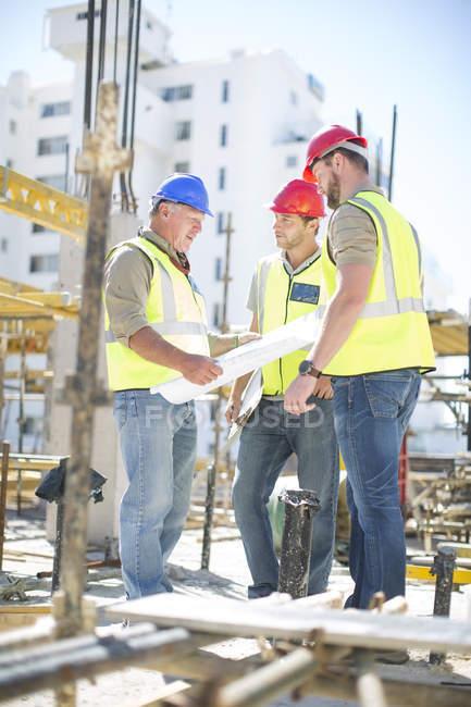 Будівельники обговорення планів будівлі на будмайданчик — стокове фото