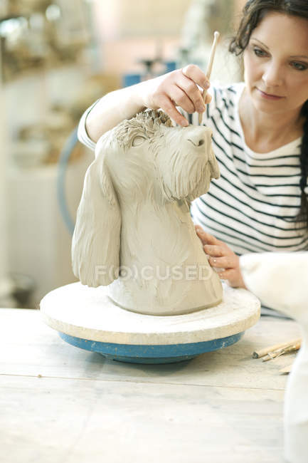 Potter in workshop working on dog figurine — Stock Photo