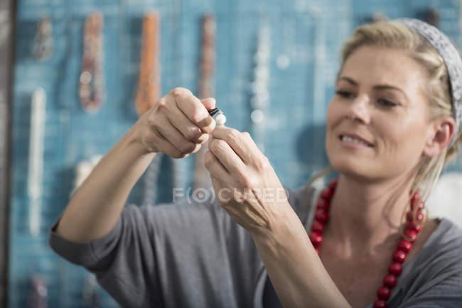Женщина работает с плоскогубцами для создания бусины ожерелье — стоковое фото