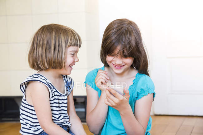 Two sisters with smartphone having fun together — Stock Photo