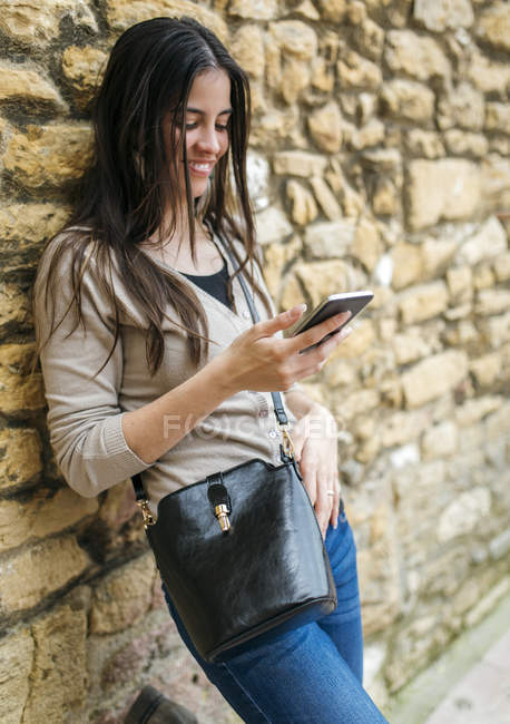 Young woman leaning against stone wall looking at smartphone — Stock Photo