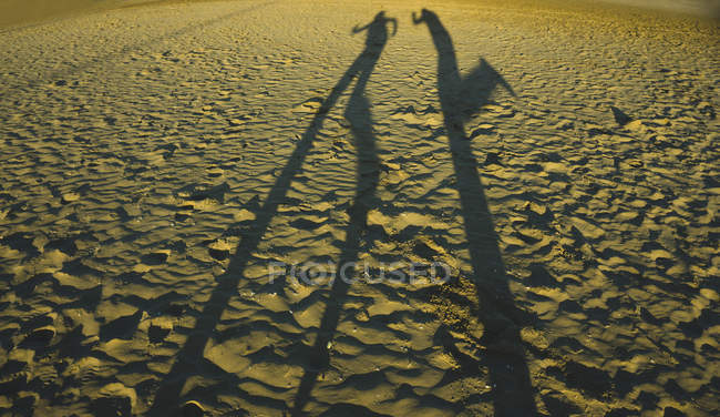 Juego de sombra de dos personas en la playa - foto de stock