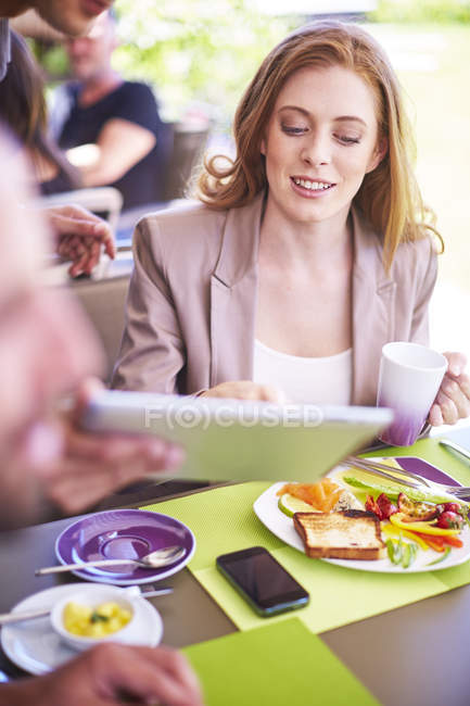 Businessman showing digital tablet to colleague at dining table — Stock Photo