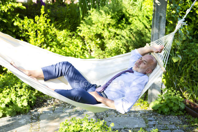 Uomo d'affari rilassante in amaca in un giardino — Foto stock