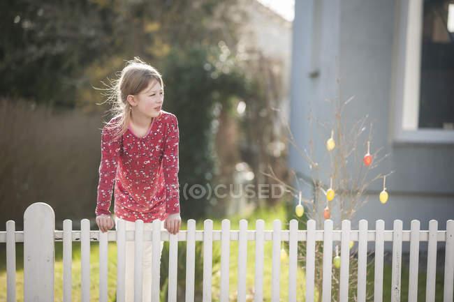 Девушка за садовым забором смотрит боком — стоковое фото