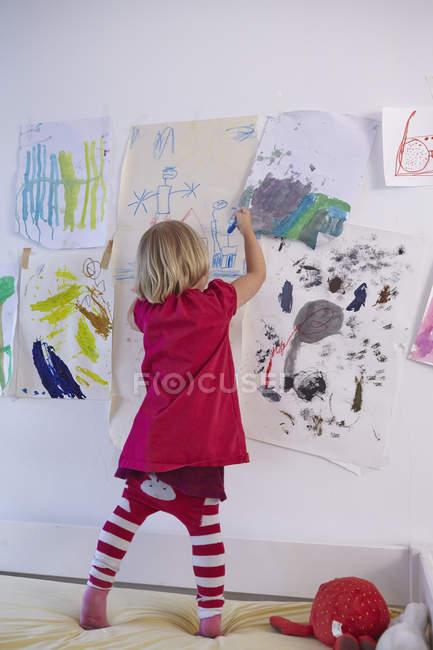 Pittura bambina sulla parete della camera dei bambini, vista posteriore — Foto stock