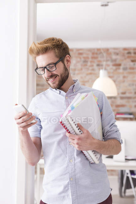 Smiling young man with cell phone and folders in office — Stock Photo