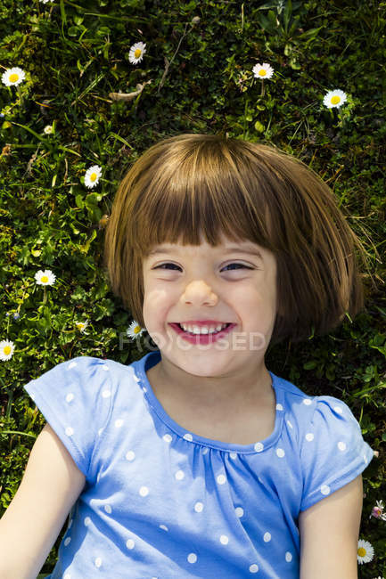 Portrait of happy little girl lying on a meadow — Stock Photo