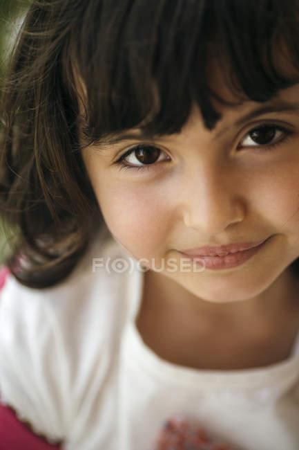 Портрет улыбающейся дошкольницы с карими глазами — стоковое фото
