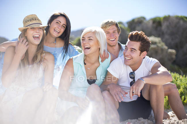 Friends socializing with laughter on the beach — Stock Photo